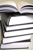 Pile of books. Stack of a book volumes with one open book resting at the top of the pile Royalty Free Stock Photo