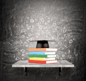 Pile of books and academic hat. A pile of books in coloured covers on a shelf, an academic hat above. Black background with scientific icons. Concept of Stock Images