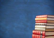 Pile of books against blue chalkboard Stock Image