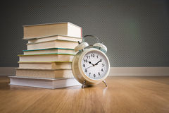 Pile of books with alarm clock. Pile of books with vintage alarm clock on parquet wooden floor, back to school concept stock image
