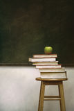 Pile of books and apple on stool Royalty Free Stock Image