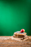 Pile of books and apple to blackboard background Royalty Free Stock Image
