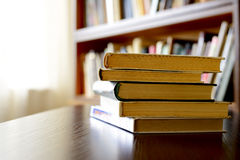 Pile of books with bookshelves in the background Stock Photography