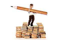 Pile of books. A boy standing on a pile of books and holding a huge pencil. Education. Isolated over white royalty free stock images