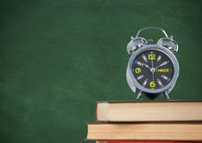 Pile of books with clock against green chalkboard Stock Images