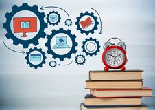Pile of books and clock with blue gear graphics against blurry grey wood panel Stock Image