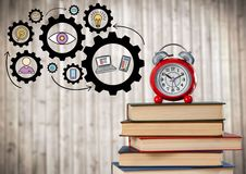 Pile of books and clock with gear graphics against blurry wood panel Royalty Free Stock Photography