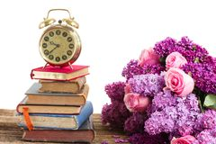 Pile of books with clock. Tower of books and clock with lilac and rose flowers isolated on white background royalty free stock image