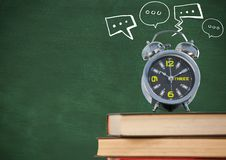 Pile of books with clock and white speech bubbles against green chalkboard Royalty Free Stock Photography