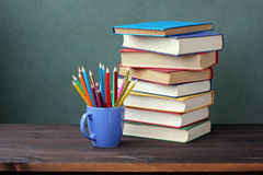 Pile of books with color covers and colored pencils in a cup. Stock Image
