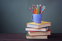 Pile of books with color covers and colored pencils in a cup. Royalty Free Stock Images