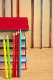 Pile of books and colored pencils on a wooden surface. Royalty Free Stock Photography