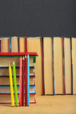 Pile of books and colored pencils on a wooden surface. Stock Image