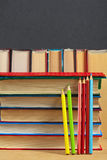 Pile of books and colored pencils on a wooden surface. Royalty Free Stock Image