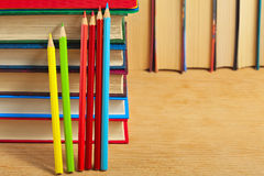 Pile of books and colored pencils on a wooden surface. Pile of books and colored pencils on a wooden surface against the background of a number of books Royalty Free Stock Photos