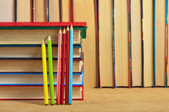 Pile of books and colored pencils on a wooden surface. Pile of books and colored pencils on a wooden surface against the background of a number of books Royalty Free Stock Images