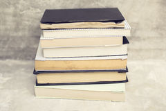 Pile of books at concrete wall background Royalty Free Stock Photography