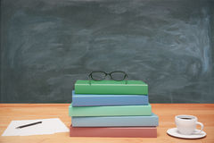 Pile of books, cup of coffee and pen on wooden table at blackboa Stock Images