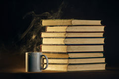 Pile of books with cup and spoon. On dark wall background Royalty Free Stock Photography