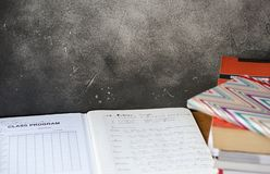 Pile of books, diary, and an open notebook with class program and French grammar notes. Pile of books, diary, and an open notebook with class program schedule on royalty free stock photography