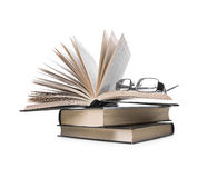 Pile of books and eyeglasses. Pile of books with one book open and eyeglasses  on white background Stock Images