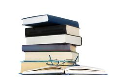 Pile of books and eyeglasses. On a open book Stock Photography