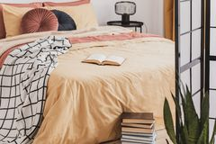 Pile of books in foot of king size bed with yellow duvet and ginger pillows stock photos