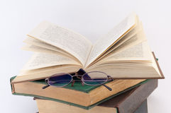 Pile of Books with Glasses. On them on a white background royalty free stock images