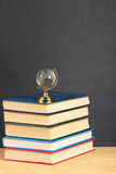 Pile of books and globe on wooden surface Stock Image