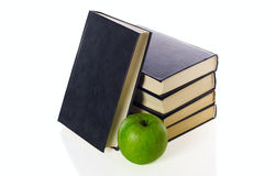 Pile of books and green apple Stock Images