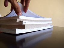 Pile of books and a hand opening a page Stock Photos