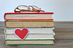 Pile of books and heart shaped bookmark Royalty Free Stock Photo