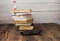 Pile of books and hourglass glasses and pencil royalty free stock photography