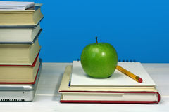Pile of books, laptop, green apple and pencil Royalty Free Stock Photography