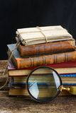 Pile of books with looking glass Stock Images