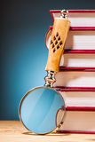 Pile of books  and magnifying glass on wooden table Stock Photo