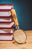 Pile of books  and magnifying glass on wooden table Royalty Free Stock Image