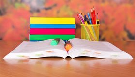 Pile of the books and markers. Pile of the books, the open book and markers on a table Royalty Free Stock Photo