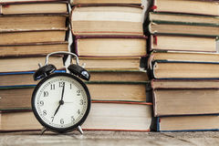 Pile of books with o& x27;clock on desk Stock Images