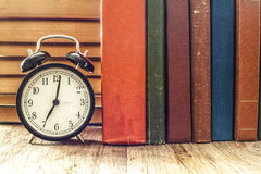 Pile of books with o& x27;clock on desk Stock Photo