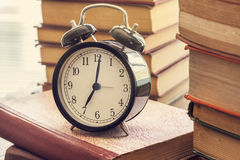 Pile of books with o& x27;clock on desk Stock Image