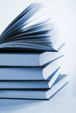 Pile of books with one book open Stock Images