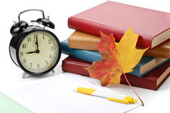 Pile of books, pen, alarm clock and autumn leaves