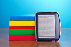 Pile of books, and the pocket electronic book Royalty Free Stock Photo