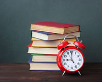 Pile of books and red alarm clock. Stock Images