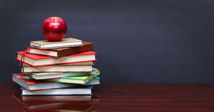 Pile of books and red apple on the desk Royalty Free Stock Photos