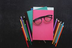 Pile of books, school stationery, glasses on slate black background. Back to school concept. Top view. Copy space. Free royalty free stock photos