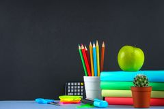 A pile of books and stationery on a chalkboard background. Work desk, education, school. Royalty Free Stock Photography