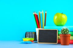 A pile of books and stationery on a chalkboard background. Work desk, education, school. A pile of books and stationery on a chalkboard background. Work desk stock photos