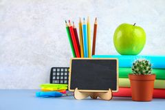 A pile of books and stationery on a chalkboard background. Work desk, education, school. A pile of books and stationery on a chalkboard background. Work desk stock photo